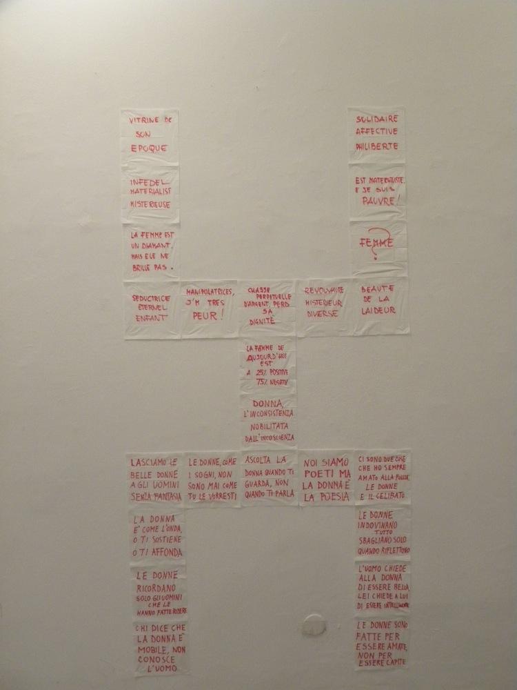 Fazzoletti carta e scritte (dimensioni variabili) Ad uomini e donne della città di Mbalmayo, Camerun è stato chiesto di scrivere su pezzi di stoffa una loro opinione sulle donne. L'insieme di questi drappi è stato montato dall'autore a formare l'icona primordiale della DONNA.